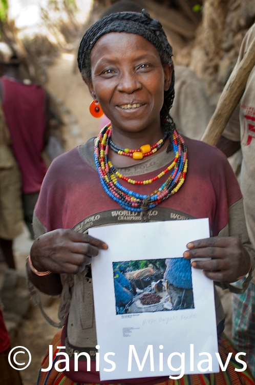 Nikke Gulgalo Kende holds print of photo I took in 2001 sorting sorghum in Busso village, Konso tribe, Ethiopia.