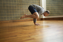 Mature Man Practicing Yoga, Crow pose