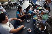 D Dong Khoi shopping street in Central Saigon. Locals having Pho (noodle soup).