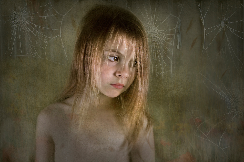 young child looking down with cobwebs in the background
