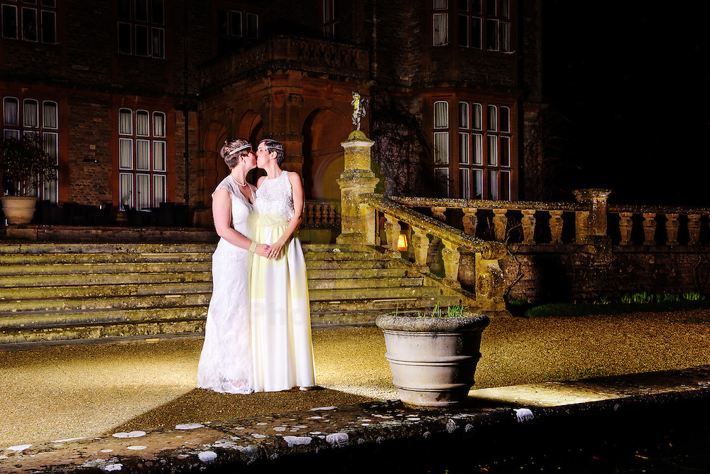 Two brides sharing a romantic kiss on their wedding day in the grounds of Eynsham Hall, North Leigh, Witney in Oxfordshire.