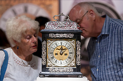 "© Licensed to London News Pictures. 28/06/2018. LONDON, UK. Visitors view ""an iconic silver basket ebony striking table clock"", 1690, by Joseph Windmills. Members of the public visit Masterpiece London, the world's leading cross-collecting art fair held in the grounds of the Royal Hospital Chelsea.  The fair brings together 160 international exhibitors presenting works from antiquity to the present day and runs 28 June to 4 July 2018.  Photo credit: Stephen Chung/LNP"