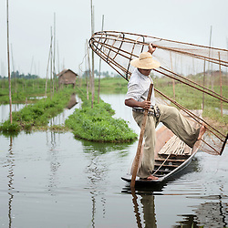 Inle Lake fisherman rowing with his feet, the traditional way to do so in the area, Inle lake, Myanmar, Asia.