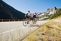 A young couple rides bikes up a mountain pass.  North Cascades of Washington State, Highway 20, USA.
