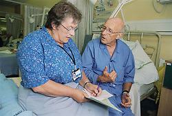 Elderly male patient sitting on hospital bed on ENT ward talking to nurse specialist,