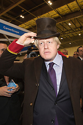 "© Licensed to London News Pictures. 22/11/2013. London, England. Pictured: Boris Johnson dons the uniform of a doorman. Boris Johnson, Mayor of London, today visited the UK's biggest jobs and careers fair ""Skills London"" at the Excel Exhibition Centre and went on a walkabout where he visited stands and performed some of the jobs on show. Photo credit: Bettina Strenske/LNP"