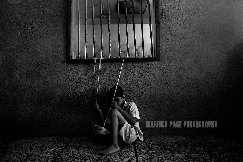 KARACHI, PAKISTAN - APRIL 18: A mentally and physically disabled boy is tied to a metal window-frame to stop him from causing harm to himself at the Edhi Home on April 18, 2008 in Karachi, Pakistan. The lack of proper facilities and staff numbers often means primitive methods are employed in order to care for the patients. The Edhi Foundation urges women give up unwanted children rather than abandon or kill in order to cover up children conceived out of wedlock, or through rape. The Edhi Foundation orphanages represent a microcosm of Pakistan's absolute poverty where children are its first casualty, tragedy and hope collide on a daily basis, and life and death are in constant flux existing only rooms apart. Pakistan is a country more than a third of it's population live in absolute poverty. As world attention fixates on Pakistan's ongoing political turmoil, generations of children are being abandoned due to Pakistan's spiraling poverty and growing instability. Some are born out of wedlock - a major social taboo - others discarded due to physical and mental disabilities, but nearly all are abandoned due to poverty. Boys and girls alike are abandoned every year, found in dumpsters mauled by rats and dogs, or left to fend for themselves on the streets of Karachi's sprawling and unforgiving metropolis. The lucky ones find their way to the Edhi Foundation orphanages. (Photo by Warrick Page)