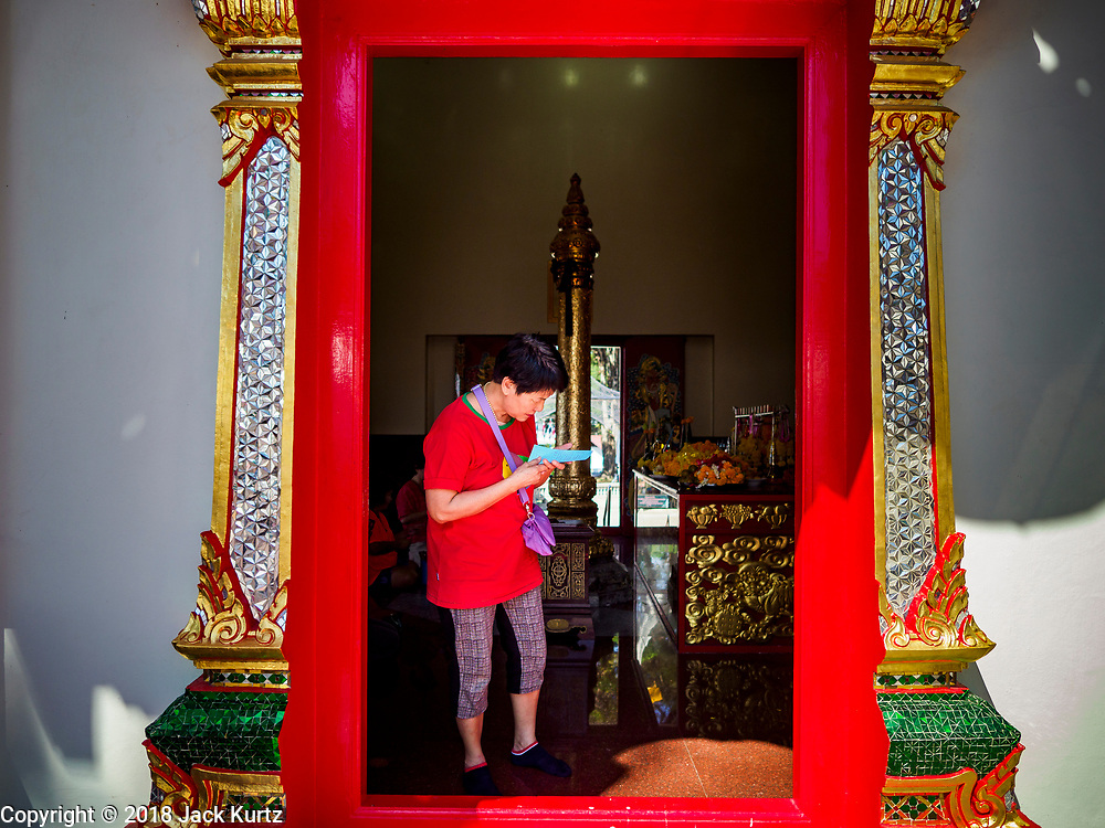 24 DECEMBER 2018 - CHANTABURI, THAILAND:  A woman reads her fortune at the city pillar shrine in Chantaburi. Most Thai cities have a city pillar shrine, which serves both to house the city spirit deity and symbolise the central power of Bangkok. Chantaburi is the capital city of Chantaburi province on the Chantaburi River. Because of its relatively well preserved traditional architecture and internationally famous gem market, Chantaburi is a popular weekend destination for Thai tourists.   PHOTO BY JACK KURTZ