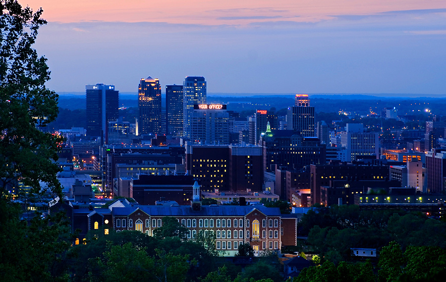 The skyline of downtown Birmingham, Alabama at dusk from Vulcan Park.  Birmingham has developed into a US banking center and is a large iron and steel producer.  The red brick building in the foreground is a building on the University of Alabama campus.