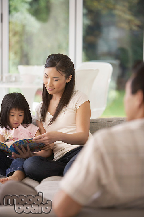 Young Mother Sitting on sofa Holding Page of Coloring Book for Daughter