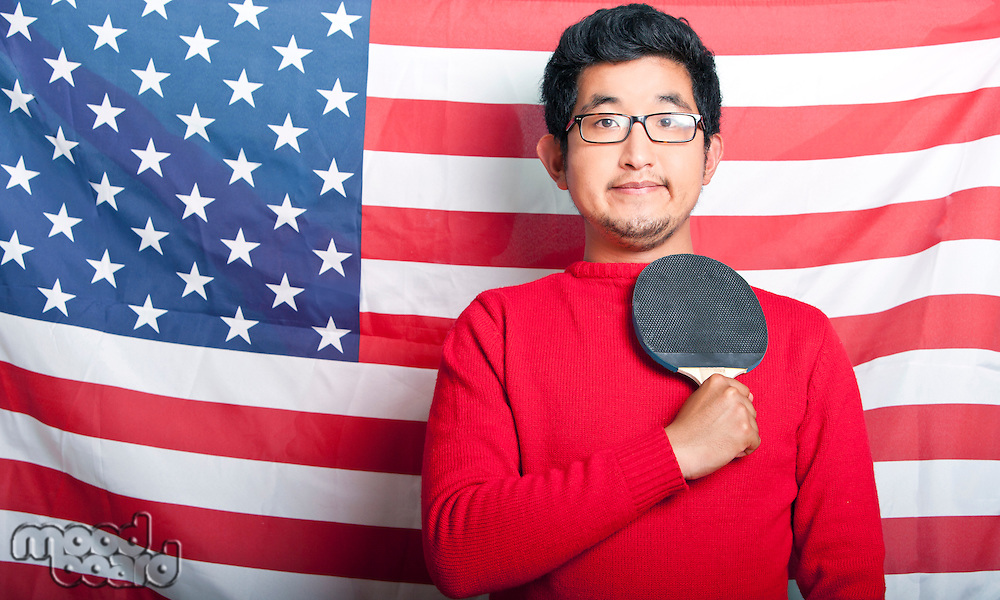 Proud Asian Man holding table tennis paddle against US Flag