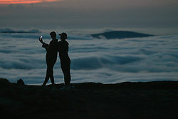 © Licensed to London News Pictures. 08/08/2020. City, UK. Two girls take a selfie on the summit of Pen-y-Fan in the Brecon Beacons, on what is expected to be the hottest day of the year across the UK. The mountain which is the highest in southern Britain, has become increasingly popular with visitors who reach the top of the peak at first light to see the sun rising from the horizon. Photo credit: Robert Melen/LNP