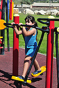 Israel, Haifa, Girl of 6 plays in a public fitness playground  - model release available