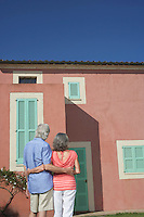 Senior couple in front of house back view