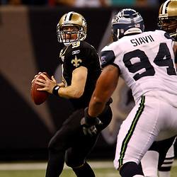 November 21, 2010; New Orleans, LA, USA; New Orleans Saints quarterback Drew Brees (9) is pressured by Seattle Seahawks defensive tackle Junior Siavii (94) during the second half at the Louisiana Superdome. The Saints defeated the Seahawks 34-19. Mandatory Credit: Derick E. Hingle