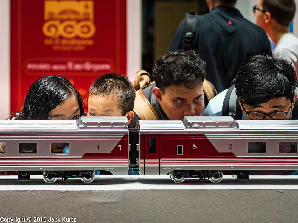 25 JUNE 2016 - BANGKOK, THAILAND:  People look at model trains in the main concourse of Hua Lamphong train station during the station's centenary celebration. Hua Lamphong opened on June 25, 1916 after six years' construction. The station was built in an Italian Neo-Renaissance-style, with decorated wooden roofs and stained glass windows. The architecture is attributed to Turin-born Mario Tamagno. There are 14 platforms, 26 ticket booths, and two electric display boards. Hua Lamphong serves over 130 trains and approximately 60,000 passengers each day. Since 2004 the station has been connected by an underground passage to the MRT (Metropolitan Rapid Transit) subway system's Hua Lamphong Station.     PHOTO BY JACK KURTZ