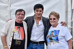 "© Licensed to London News Pictures. 23/07/2017. London, UK. Fans meet Eddy Popescu, an Elvis tribute singer.  Fans attend the capital's first ever ""Elvis Fest"" to mark the 40th anniversary of the King of Rock N' Roll's death.  Taking place in Parsloes Park, Dagenham, the festival includes a variety of tribute acts representing Elvis through his career. Photo credit : Stephen Chung/LNP"