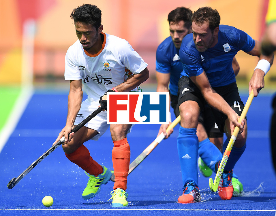 India's Kothajit Khadangbam (L) tries to get past Argentina's Agustin Mazzilli (C) and Juan Gilardi during the men's field hockey Argentina vs India match of the Rio 2016 Olympics Games at the Olympic Hockey Centre in Rio de Janeiro on August, 9 2016. / AFP / MANAN VATSYAYANA        (Photo credit should read MANAN VATSYAYANA/AFP/Getty Images)