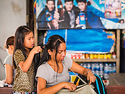 "03 JANUARY 2017 - BANGKOK, THAILAND: A girl does her mother's hair while they wait to board their bus at Ekkamai Bus Terminal in Bangkok Tuesday. Travelers flocked to Bangkok's bus and train stations Tuesday, the last day of the long New Year's weekend in Thailand. The New Year holiday in Thailand is called the ""seven deadly days"" because of the number of fatal highway and traffic accidents. As of Monday Jan 2, 367 people died in highway accidents over the New Year holiday in Thailand, a 25.7% increase over the same period in 2016.        PHOTO BY JACK KURTZ"