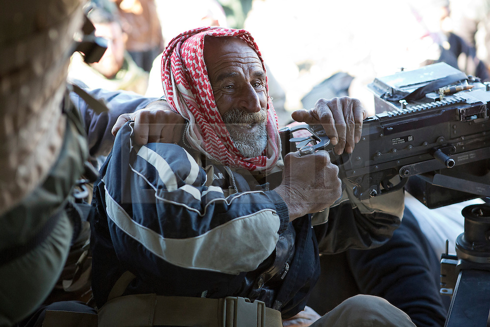 © Licensed to London News Pictures. 11/12/2014. Sinjar Mountains, Iraq. An elderly Yazidi refugee hangs from an M240 machine gun as he attempts to climb in to an Iraqi Air Force Mi-17 helicopter, that will evacuate both he and his family from Mount Sinjar.<br /> <br /> Although a well publicised exodus of Yazidi refugees took place from Mount Sinjar in August 2014 many still remain on top of the 75 km long ridge-line, with estimates varying from 2000-8000 people, after a corridor kept open by Syrian-Kurdish YPG fighters collapsed during an Islamic State offensive. The mountain is now surrounded on all sides with winter closing in, the only chance of escape or supply being by Iraqi Air Force helicopters. Photo credit: Matt Cetti-Roberts/LNP