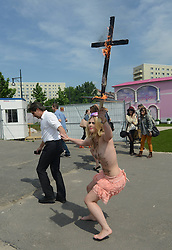59653690 .A topless protester holds a burning crucifix during the Protest against the Opening of the controversial touring exhibition of Barbie in Berlin. Several Hundred Activists  demonstrate against the Role-image by Barbie by Women on Beauty Slenderness and Consumption, Berlin, Germany, May 16, 2013.   Photo by: imago / i-Images. UK ONLY