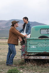 sexy cowboy with a beautiful woman by a vintage truck on a ranch