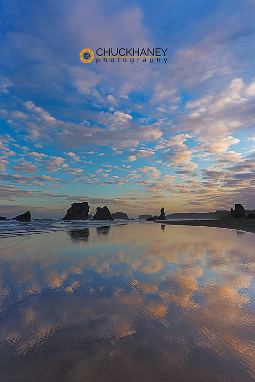 Clouds reflect in wet sand at sunrise at Bandon Beach in Bandon, Oregon, USA