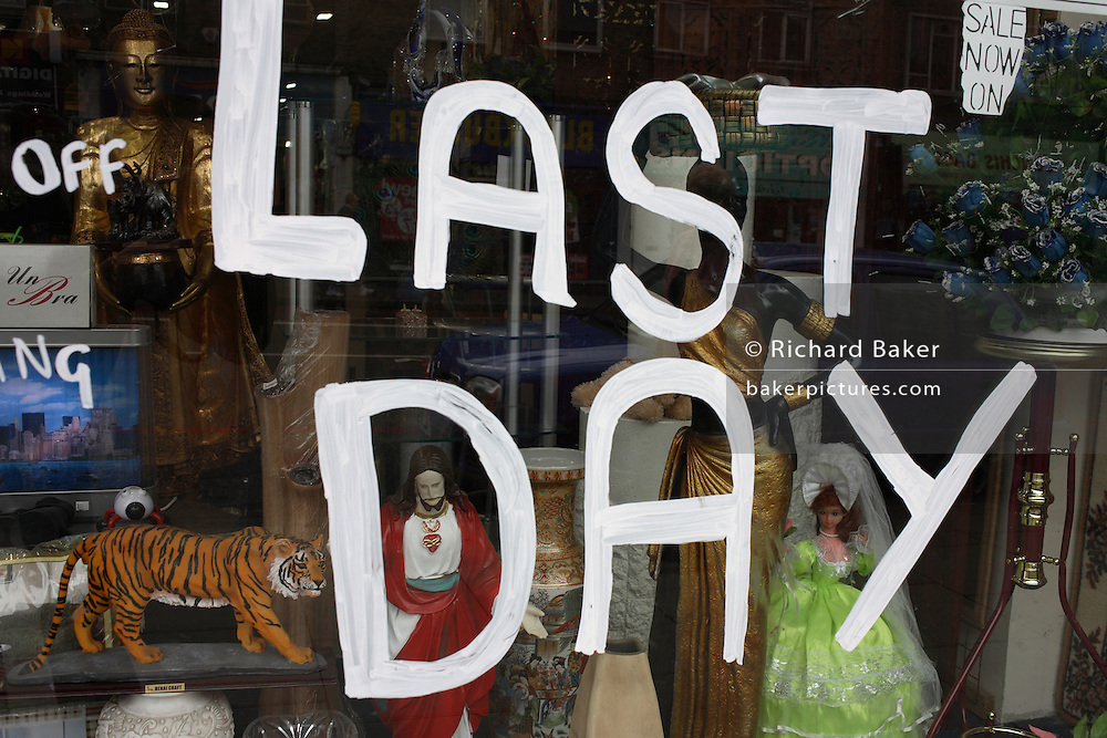 Seen through a junk shop window in north London, the large letters Last Day have been painted in white emulsion paint on the pane of glass. Between the letters are figures and bric-a-brac on sale in this budget store. A tiger model; a Jesus figure; a doll in a green dress. 'Last Day' is also ironic in a Biblical context as it was taken a few days after the Day of Resurrection and Easter.