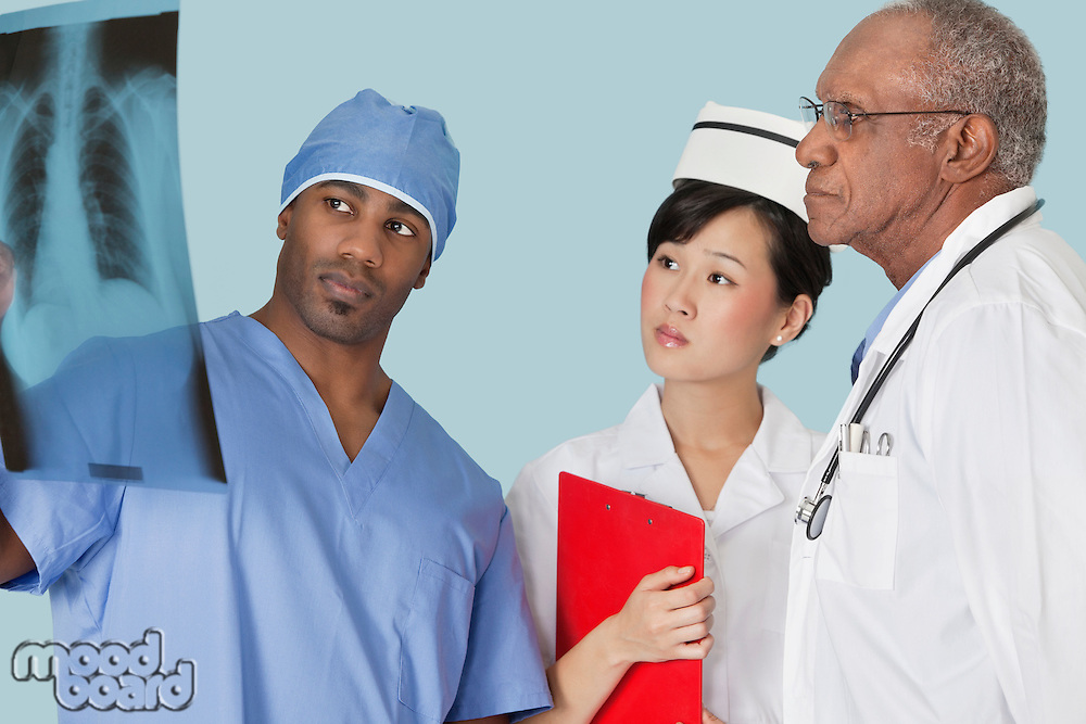 Multi ethnic doctors examining x-ray report over light blue background