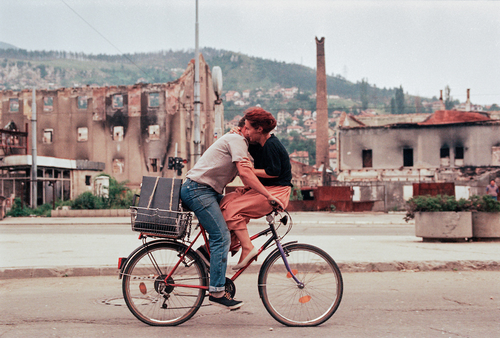 A couple shares a bicycle in wartime Sarajevo.