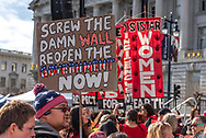 "San Francisco, USA. 19th January, 2019. The Women's March San Francisco begins with a rally at Civic Center Plaza in front of City Hall. During the rally, a man holds a sign criticizing Trump's wall and the shutdown, reading ""Screw the damn wall. Reopen the government now!"" Credit: Shelly Rivoli/Alamy Live News"