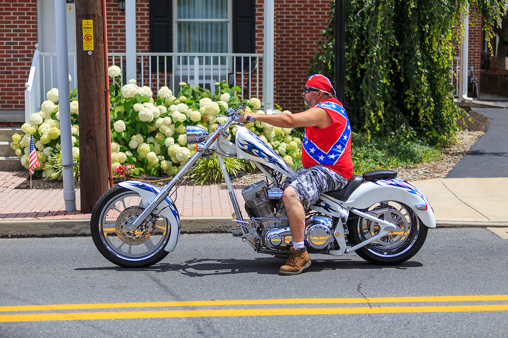 Gettysburg, PA – July 2, 2016: A motorcyclist wearing a confederate flag shirt on a motorcycle in Gettysburg.