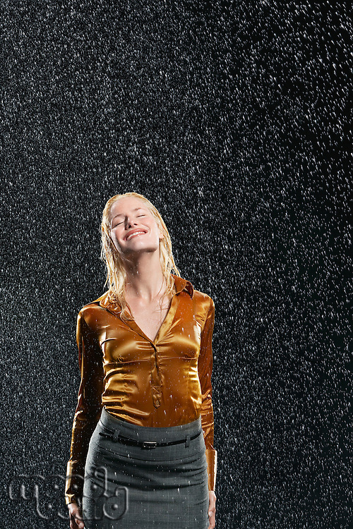 Woman Standing in Rain letting raindrops fall on face
