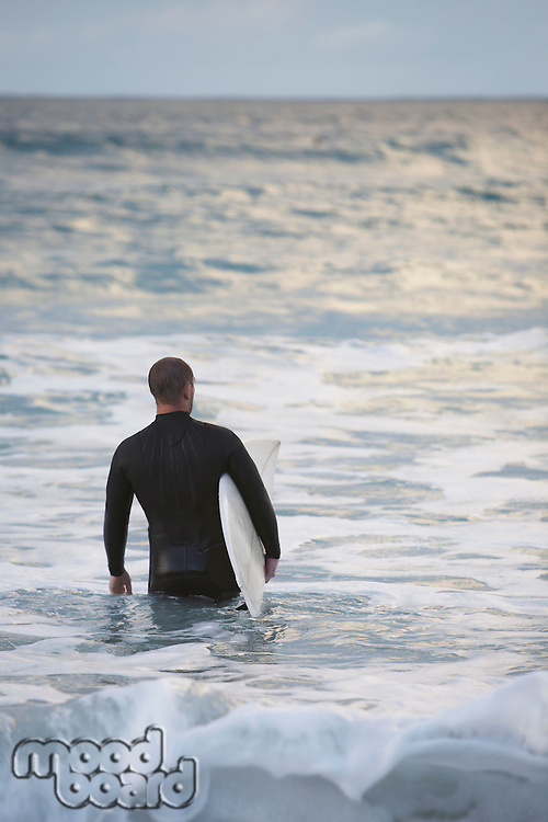 Surfer carrying surfboard into sea back view
