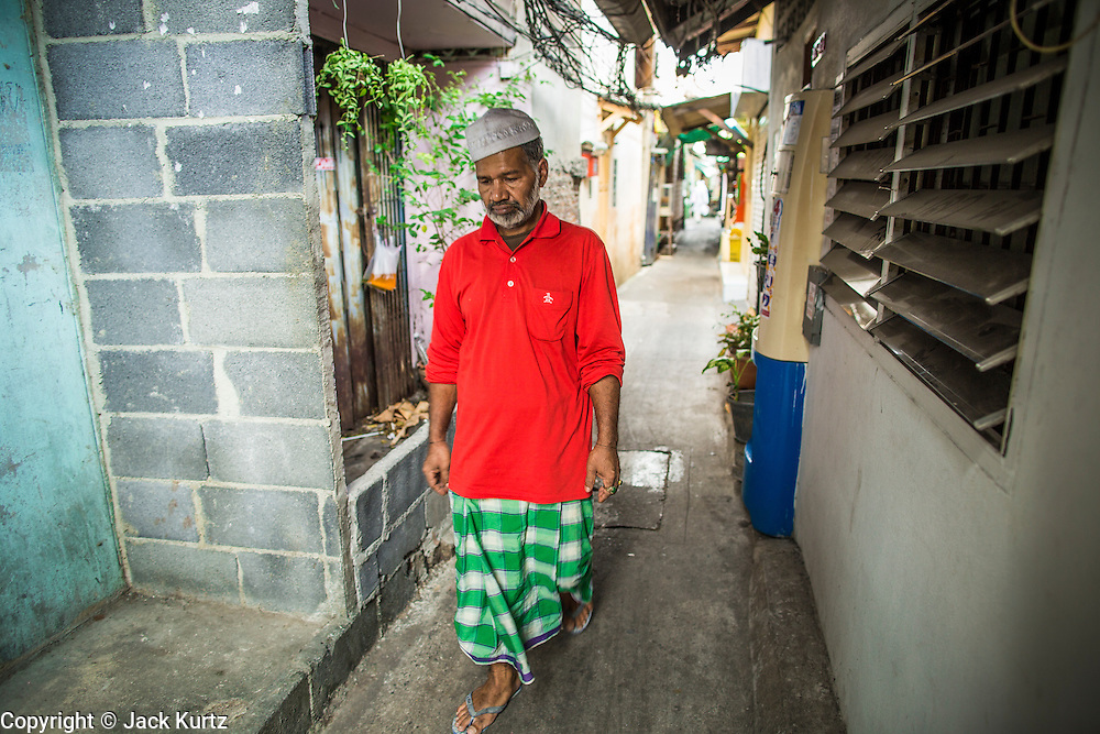 "10 JANUARY 2013 - BANGKOK, THAILAND:    A Muslim man walks through the Baan Krua neighborhood in Bangkok. The Ban Krua neighborhood of Bangkok is the oldest Muslim community in Bangkok. Ban Krua was originally settled by Cham Muslims from Cambodia and Vietnam who fought on the side of the Thai King Rama I. They were given a royal grant of land east of what was then the Thai capitol at the end of the 18th century in return for their military service. The Cham Muslims were originally weavers and what is known as ""Thai Silk"" was developed by the people in Ban Krua. Several families in the neighborhood still weave in their homes.   PHOTO BY JACK KURTZ"