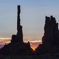 The Totem Pole silhouettes at sunrise with a sun-star peeking through. Monument Valley Navajo Tribal Park, Arizona
