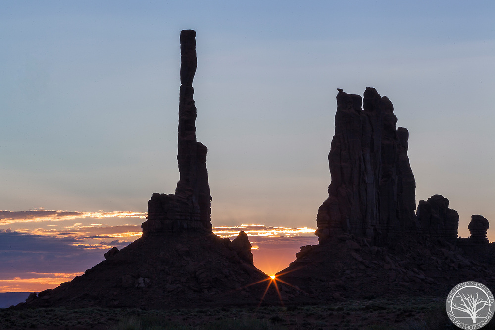 The Totem Pole silhouettes at sunrise with a sun-star peeking through. Monument Valley Navajo Tribal Park, Arizona