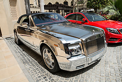 Silver Rolls-Royce luxury car parked  outside luxury hotel in Dubai United Arab Emirates