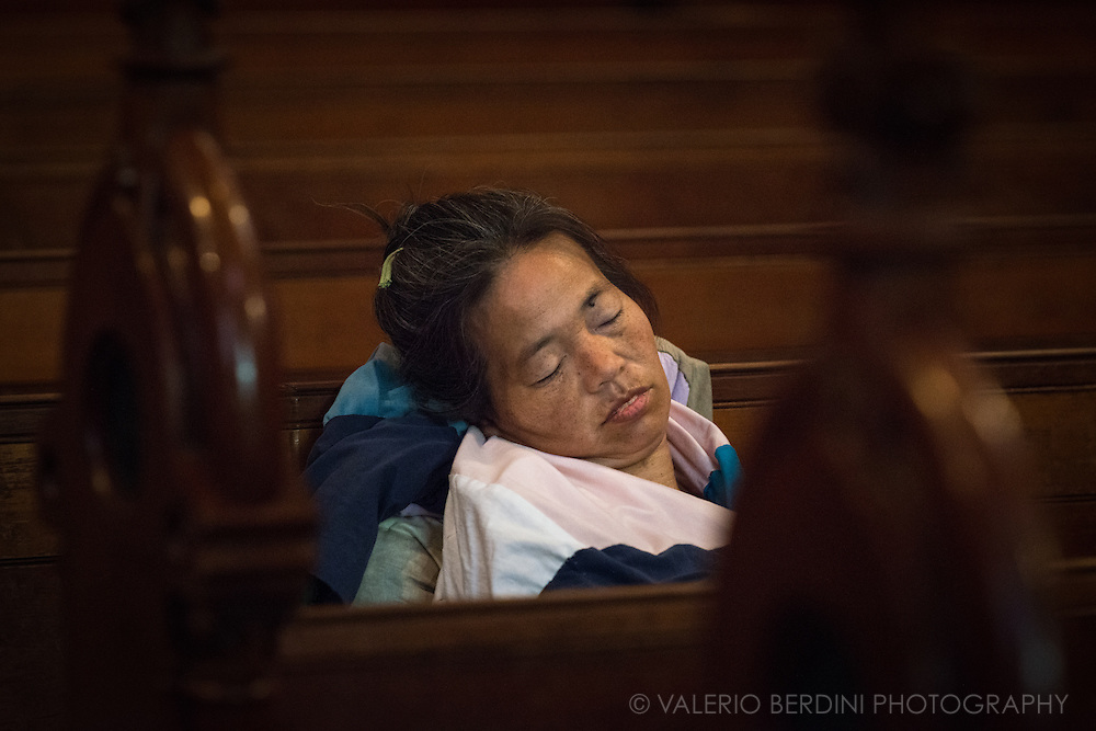 A homeless woman take a nap surrounded by her belongings inside Old South Church in Boylston Street, one of the luxurious shopping streets in Boston, Massachusetts.