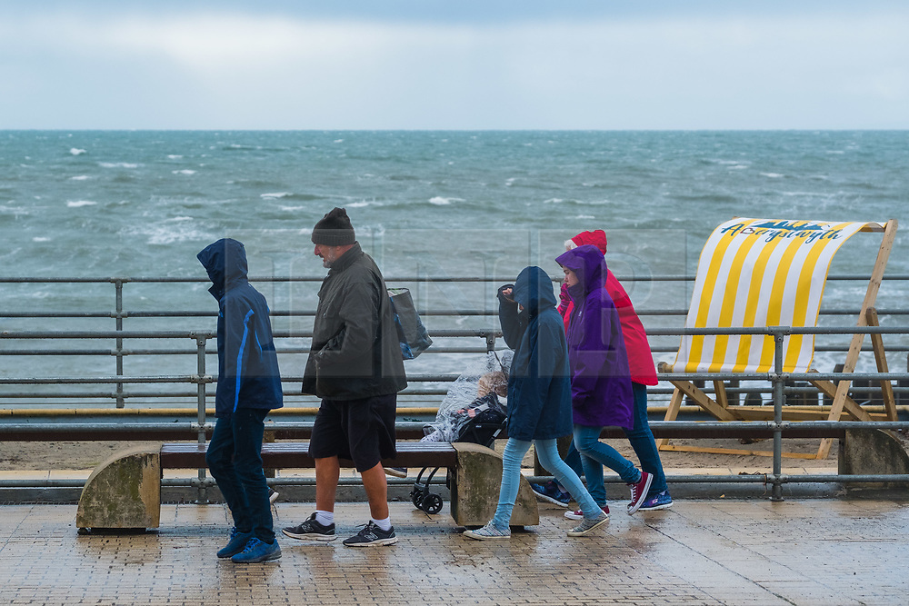 © Licensed to London News Pictures<br /> Aberystwyth, UK. 26/10/2018. A family walks along the promenade as bitterly cold northerly winds blow over Aberystwyth on the Cardigan Bay coast of west Wales as the weather turns decidedly wintry. photo credit Keith Morris/ LNP