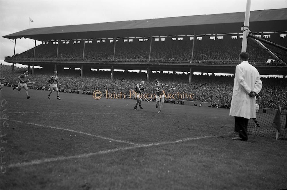 06/09/1964<br /> 09/06/1964<br /> 6 September 1964<br /> All-Ireland Senior Final: Tipperary v Kilkenny at Croke Park, Dublin.<br /> Tipperary left full-forward, S. McLoughlin (left) hits the ball with his right hand to score a goal, after he had dropped his hurl. The player on the left with the agonised look is Kilkenny full back, P. Dillon.