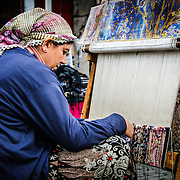 A woman uses a loom to weave a Turkish carpet at the Arastar Bazaar, a small bazaar next to the Sultanahment Camii (Blue Mosque) in Istanbul, Turkey.