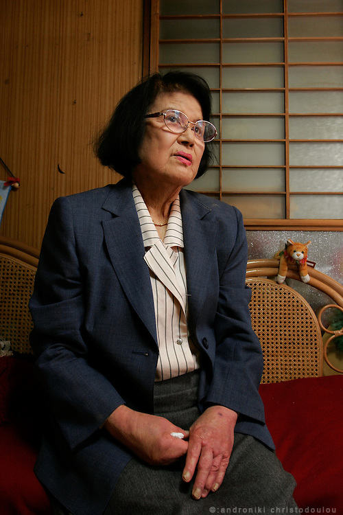 MICHIKO YAMAOKA Hiroshima A-Bomb survivor in her flat. She was 15 years old and a third-year student at a girl's middle school. She was working as a mobilized student at the Hiroshima Central Telephone Office and at the time of the bombing she was on her way to work. She was badly injured and would have died under a wall that collapsed on her, if her mother wouldn't have come to her rescue. Her face was disfigured by the injuries and by keloids that grew on it. Her condition made her want to die but her mother's support helped her regain the will for life. Later she went to the US and had 27 surgical operations on her keloids. She is one of the survivors who tell their stories in the Hiroshima Peace Memorial Museum and she has been even traveling overseas to tell her story.