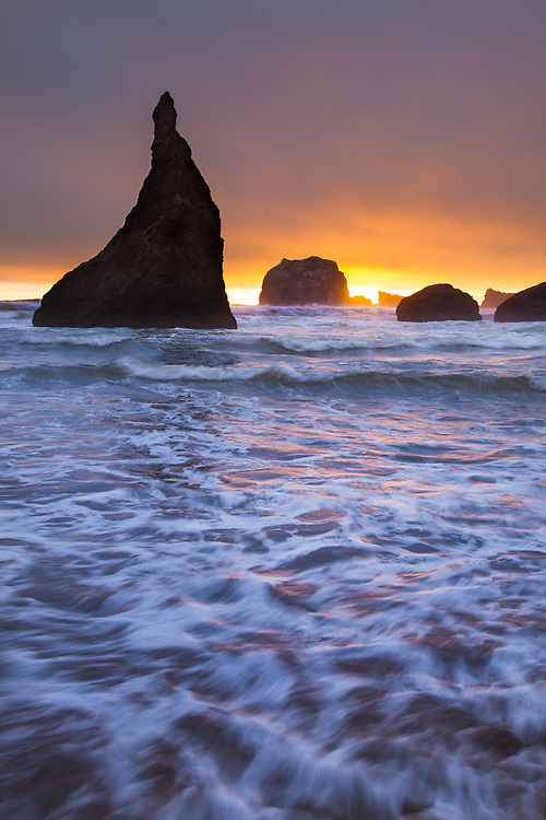 The incoming high tide at Face Rock Wayside, on the Oregon coast near Bandon, reflects the warm tones of sunset light as it crashes onshore.