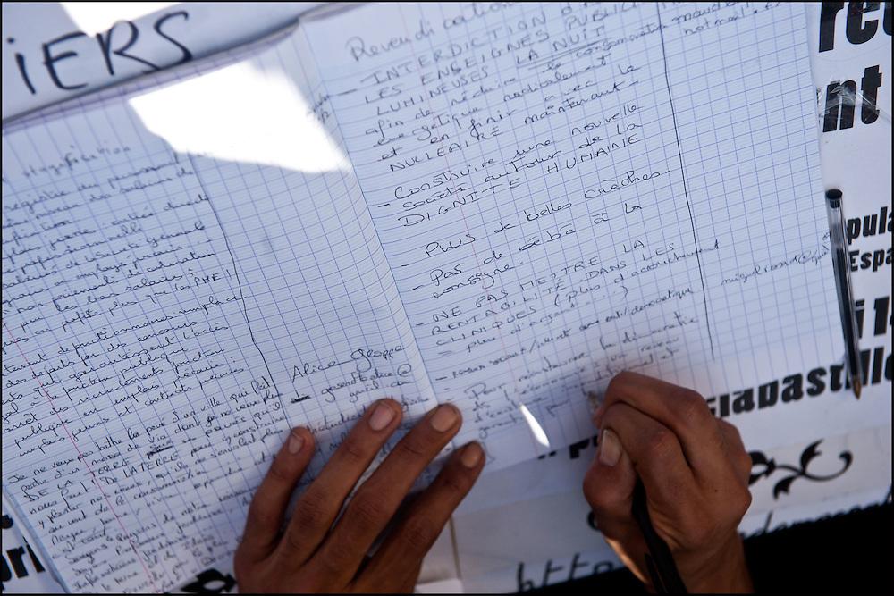 Tout le monde peut venir ecrire un mot dans le cahier des doleances lors du rassemblement d'un millier de personne en soutien aux mouvement des indignados en Espagne, Non violent et fonctionnant de façon democratique le mouvement tente de rester dormir sur la place de la Bastille mais les forces de polices les évacuent en debut de soiree - Place de la Bastille à Paris le 29 Mai 2011. ©Benjamin Girette/IP3Press