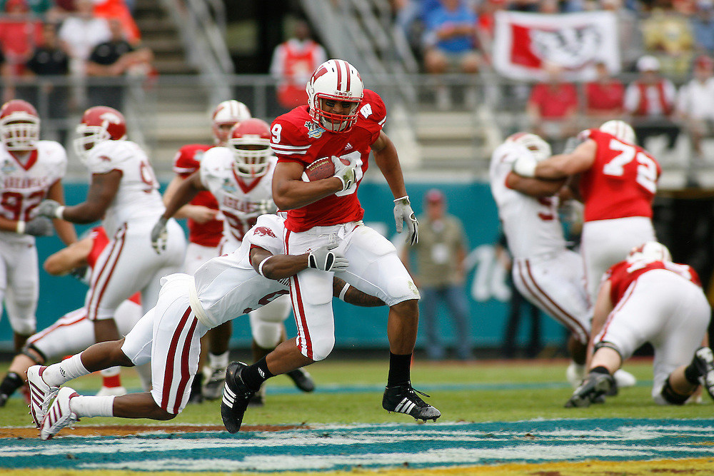 University of Wisconsin tight end Travis Beckum runs past University of Arkansas defensive back Matterral Richardson after making a catch during the Wisconsin Badgers 17-14 victory over the Arkansas Razorbacks on January 1, 2007 at the Florida Citrus Bowl Stadium in Orlando, Florida.