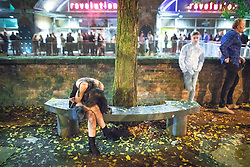 © Licensed to London News Pictures . 29/10/2016 . Manchester , UK . A woman sits slumped on a bench at Deansgate Locks . Revellers on a night out , many in fancy dress , on the weekend before Halloween . Photo credit : Joel Goodman/LNP