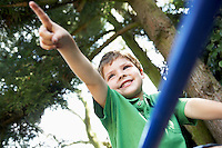 Young Boy sitting on monkey bars pointing close up