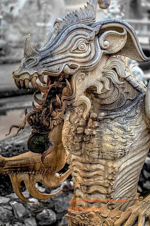 Thai Terrorist:  The spectacular Buddhist White Temple is littered with innumerable statues of horrific creatures like this lean reptilian being that arises from the waters of Wat Rong Khun, Chiang Rai Thailand.