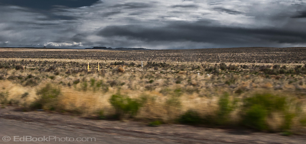 threatening clouds cross the barren lands of northwestern New Mexico along a US highway